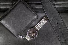 Mężczyzna eleganccy akcesoria czarna skóra, portfel, pasek i stalowy zegarek na tle czarna teczka, obrazy royalty free