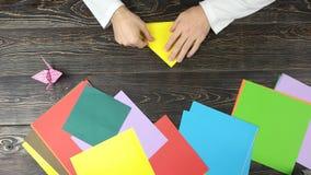 Mężczyzna falcowania papier jako trójbok zbiory
