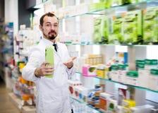 Mężczyzna farmaceuta pokazuje asortyment obraz stock