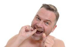 Mężczyzna flossing jego zęby z stomatologicznym floss Zdjęcie Royalty Free