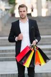 Mężczyzna formalny kostium niesie torba na zakupy Facet niesie wiązek torba na zakupy Zyskowne transakcje robi zakupy na czarnym  zdjęcia stock