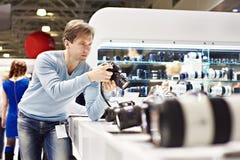 Mężczyzna fotograf bada cyfrową SLR kamerę w sklepie zdjęcia stock