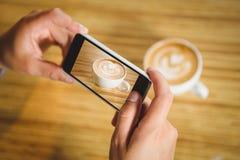 Mężczyzna fotografuje jego cappuccino z kawową sztuką zdjęcia royalty free
