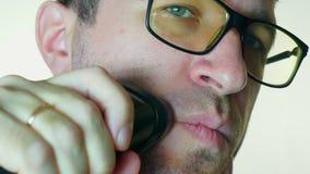 Mężczyzna goli jego policzek z elektryczną żyletką na białym tle, zdjęcie wideo