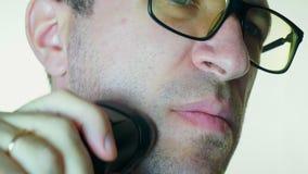 Mężczyzna goli jego policzek z elektryczną żyletką, zła żyletka zdjęcie wideo