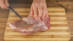 Mężczyzna gotuje mięso na tnącej desce na stole od starych drewnianych desek Męska ręka z nożowym ciie up kawałek mięso zbiory