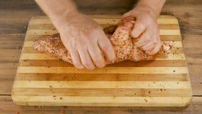 Mężczyzna gotuje mięso na tnącej desce na stole od starych drewnianych desek Męskie ręki kropią pikantność i mią kawałek zbiory wideo