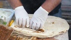 Mężczyzna gotuje robić ekmek z rybą przy ulicznym rynkiem, ręki w rękawiczki zbliżeniu zbiory