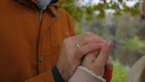 Mężczyzna grże kobiety ` s ręki Państwa młodzi mienia ręki i grżą each inny w parku trzymaj ręce mężczyzny kobiety Zdjęcie Royalty Free