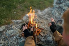 Mężczyzna grże ręki blisko ogniska zdjęcia royalty free