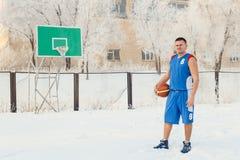 Mężczyzna gracz koszykówki w błękitnych sporta munduru stojakach na boisko do koszykówki i chwytach koszykówka w jego rękach w zi Obraz Royalty Free