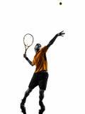 Mężczyzna gracz w tenisa przy usługową porci sylwetką Obraz Royalty Free