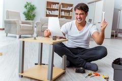 Mężczyzna gromadzić meble w domu obrazy stock
