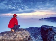 Mężczyzna gubjący w gęstych mgieł skałach Wycieczkowicz wspinał się w górę samotnie odsłonięty szczyt zdjęcie stock