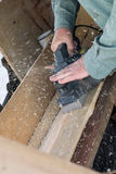 Mężczyzna hebluje deskę drewno z elektrycznym samolotem obrazy royalty free