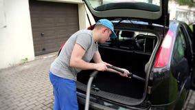 Mężczyzna hoovering samochodowego bagażnika przed wycieczką zdjęcie wideo