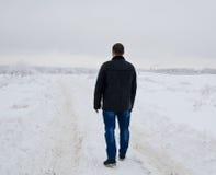 Mężczyzna iść na śnieżnym polu Zdjęcia Stock