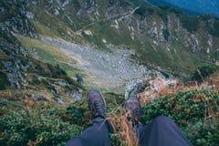 Mężczyzna iść na piechotę, siedzący na krawędzi wąwóz Punkt widzenia, ostrość na tle, Karpackie góry, Marmarosh zdjęcie royalty free