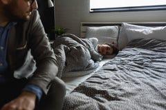Mężczyzna iść pracować w ranku opuszcza kobiety w łóżku obraz stock