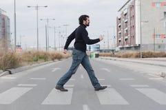 Mężczyzna iść przez zebry skrzyżowania Fotografia Royalty Free