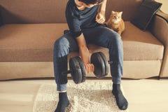 Mężczyzna iść wewnątrz dla sportów z dumbbells z kotem w domu zdjęcia royalty free