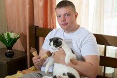 Mężczyzna i śmieszny kota łasowania lody konusujemy w łóżku Zdjęcia Stock