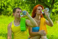 Mężczyzna i żeńska woda pitna od butelek Obraz Stock