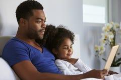 Mężczyzna i córki obsiadanie w łóżkowym dopatrywanie komputerze, talia up obrazy stock