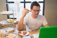 Mężczyzna i jego komputer z główkowaniem stawiamy czoło przy herbacianym czasem Obrazy Stock