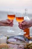 Mężczyzna i kobieta brzęczy win szkła z różanym winem przy zmierzchu bea Zdjęcie Royalty Free