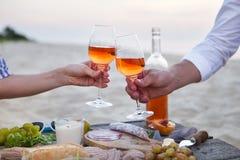 Mężczyzna i kobieta brzęczy win szkła z różanym winem przy zmierzchu bea Fotografia Stock
