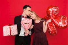 Mężczyzna i kobieta dajemy innym prezentom, trzymamy each, prezentów pudełka i balony, walentynki pojęcie w studiu na czerwonym t fotografia royalty free