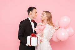 Mężczyzna i kobieta dajemy innym prezentom, trzymamy each, prezentów pudełka i balony, walentynki pojęcie w studiu na różowym tle zdjęcia royalty free