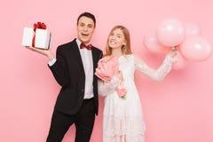 Mężczyzna i kobieta dajemy innym prezentom, trzymamy each, prezentów pudełka i balony, walentynki pojęcie w studiu na różowym tle fotografia royalty free