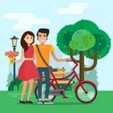 Mężczyzna i kobieta na dacie w parku z kwiatami i rowerem Zdjęcia Stock
