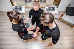 Mężczyzna i kobieta na ems szkoleniu z ogłoszenie towarzyskie trenerem obraz royalty free