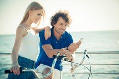 Mężczyzna i kobieta na rowerowym używa smartphone wpólnie fotografia stock
