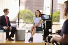 Mężczyzna i kobieta na secie dla TV przeprowadzamy wywiad, skupiamy się na przedpolu, Fotografia Royalty Free