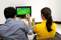 Mężczyzna i kobieta oglądamy Futbolowego dopasowanie na tv Zdjęcia Royalty Free