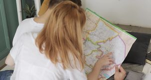 Mężczyzna i kobieta planujemy podróży trasę samochodową wycieczką używać mapę zdjęcie wideo