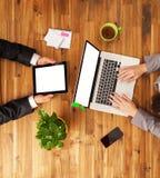 Mężczyzna i kobieta pracuje na urządzeniach elektronicznych Zdjęcie Stock