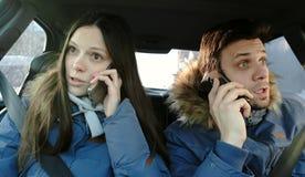 Mężczyzna i kobieta przysięga ich telefony komórkowych siedzi w samochodzie obraz stock