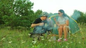 Mężczyzna i kobieta siedzimy blisko namiotu i jemy smażącej herbaty mięsa i napoju