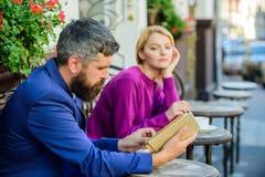 Mężczyzna i kobieta siedzimy kawiarnia taras Dziewczyna ciekawił co on czyta Literatura wspólny interes Dlaczego znajdować dziewc obraz stock