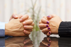 Mężczyzna i kobieta siedzimy przy biurkiem z rękami spinać małżeński problem fotografia royalty free