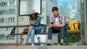 Mężczyzna i kobieta siedzimy wpólnie przy przewiezioną stacją Trzymają nowożytnych gadżety i zabawiają z internetem zbiory wideo
