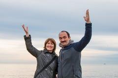 Mężczyzna i kobieta stoi w pobliżu podnosiliśmy ich ręki w powitaniu Morze i niebo w tle zdjęcia stock
