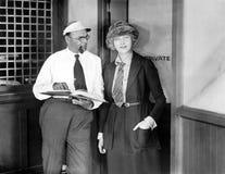 Mężczyzna i kobieta stoi wpólnie w biura drzwi (Wszystkie persons przedstawiający no są długiego utrzymania i żadny nieruchomość  Zdjęcia Royalty Free
