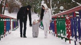 Mężczyzna i kobieta trzymamy rękojeści ich młody syn, on tylko ostatnio uczyliśmy się chodzić, w ten sposób robimy mię clumsily R zdjęcie wideo