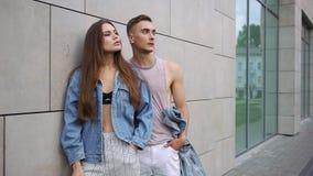 Mężczyzna i kobieta ubieraliśmy w przypadkowej ulica stylu pozie zanim popielata ściana zbiory wideo